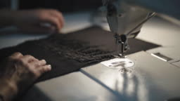 Tailor cutting textile with Sewing machine during the night in low light