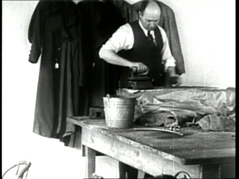 a tailor irons clothing in his laundry shop - tailor stock videos & royalty-free footage
