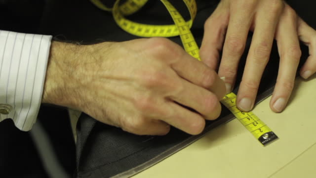Tailor is using a measuring tape and making marks on a suit. Man hands close up working on his small business.