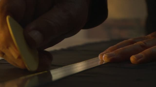 A tailor marks a piece of fabric with a yardstick and yellow chalk. Available in HD.