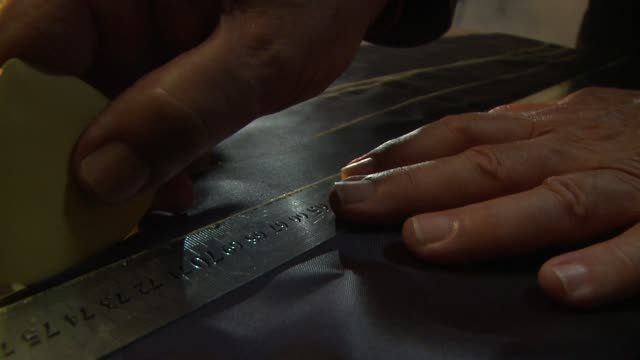 A tailor marks black fabric with a yardstick and yellow chalk. Available in HD.