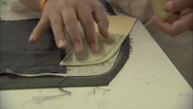 stockvideo's en b-roll-footage met a tailor measures and cuts a garment. - kleermaakster