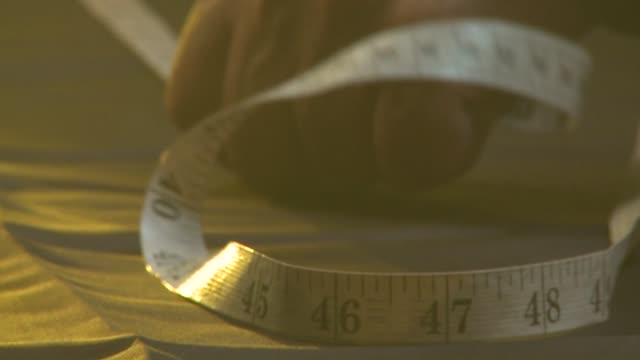 A tailor measures and pins a piece of fabric. Available in HD.