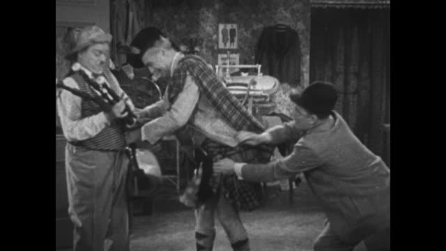 vídeos y material grabado en eventos de stock de 1934 tailor removes irritable but appreciative man's kilt for pressing - plancha