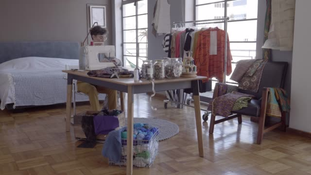 stockvideo's en b-roll-footage met tailor sewing textile at table in bedroom - milleniumgeneratie