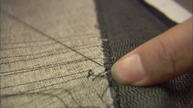stockvideo's en b-roll-footage met a tailor stitches material. - kleermaakster
