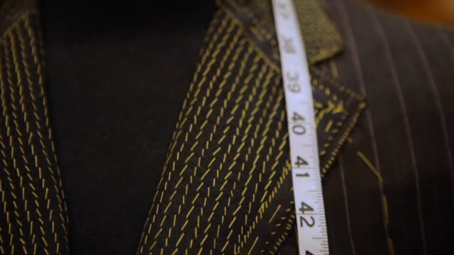 tailored men's suits on a rack - tailored clothing stock videos & royalty-free footage