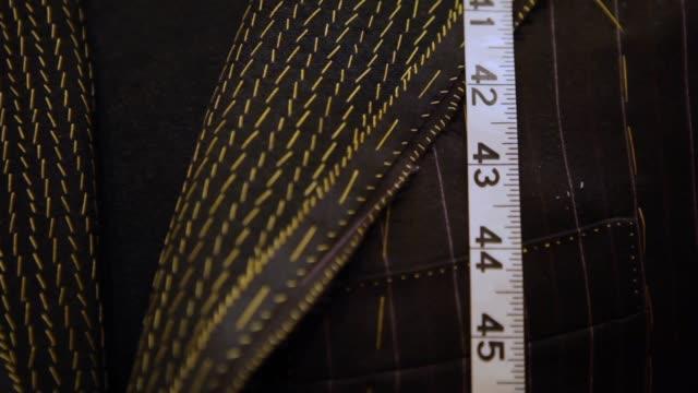 maßgeschneiderte herrenanzüge auf einem rack - maßkonfektion stock-videos und b-roll-filmmaterial