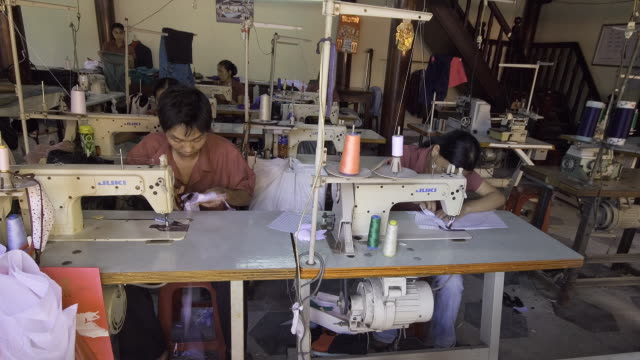 vídeos de stock e filmes b-roll de ms zi t/l tailors toil to sew garments in sweatshop factory / hoi an, quang nam province, vietnam. - indústria têxtil