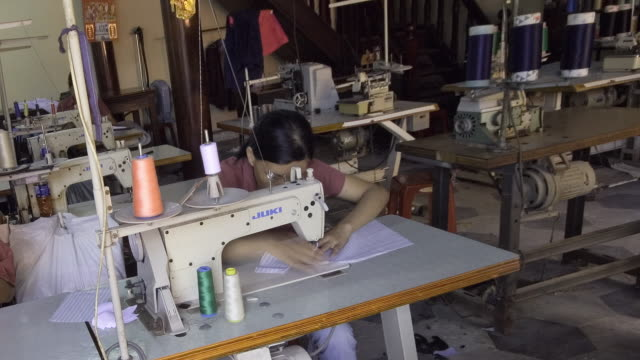 vídeos de stock e filmes b-roll de ms pan t/l tailors toil to sew garments in sweatshop factory / hoi an, quang nam province, vietnam. - indústria têxtil
