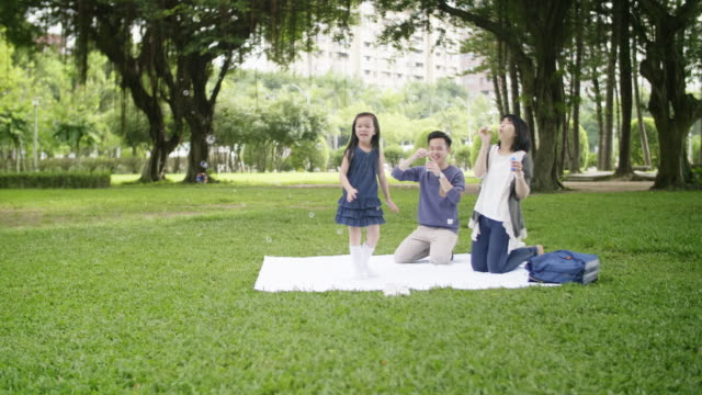 taiwanese family blowing bubbles in park - taipei stock videos & royalty-free footage