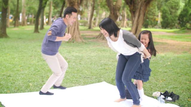 vídeos de stock, filmes e b-roll de família taiwanesa que joga jogos no parque - brincadeira de pegar