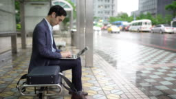 Taiwanese man using laptop and talking on phone on the bus station