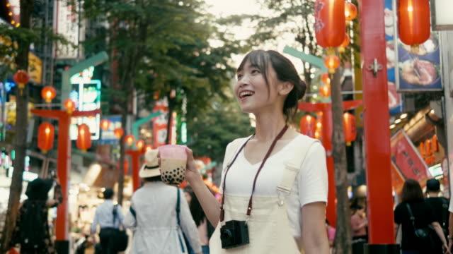 vídeos y material grabado en eventos de stock de mujer millenial taiwanesa bebiendo té de burbujas y waliking en el distrito comercial de ximending (cámara lenta) - taipei