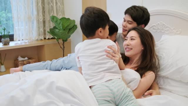 台湾の母親と父親は、彼らの男の子とベッドで遊んで - プロレスごっこ点の映像素材/bロール