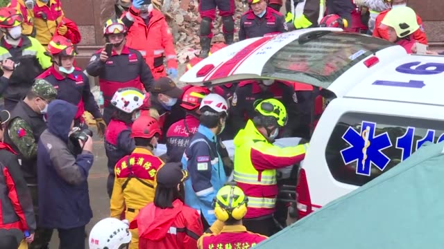Taiwanese rescuers pull the body of a hotel staffer from a dangerously leaning apartment block that was partially toppled by a quake