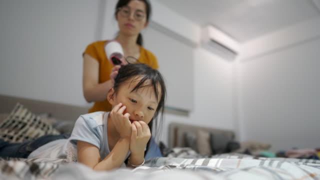 台湾の女性は寝室で彼女の娘の髪を乾燥させる - 乾燥点の映像素材/bロール
