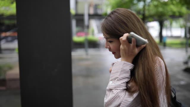 vídeos de stock, filmes e b-roll de mulher taiwanesa que emite a mensagem de voz na rua - voz