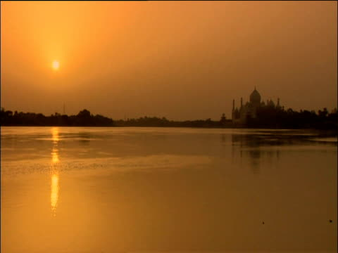 Taj Mahal across river silhouetted in orange sunset birds fly past in foreground Agra
