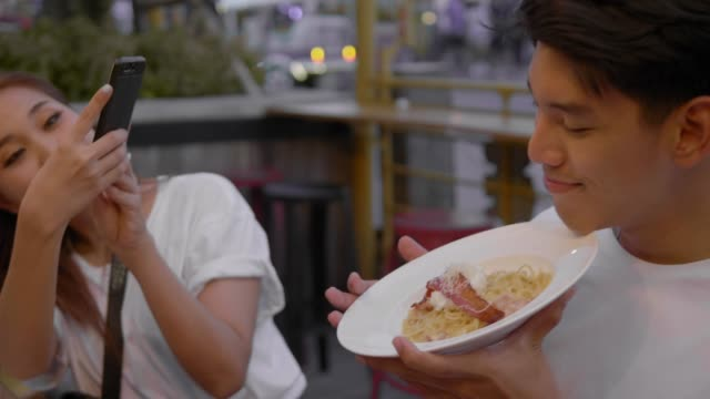 take a photo of food : young asian couple - street food stock videos & royalty-free footage