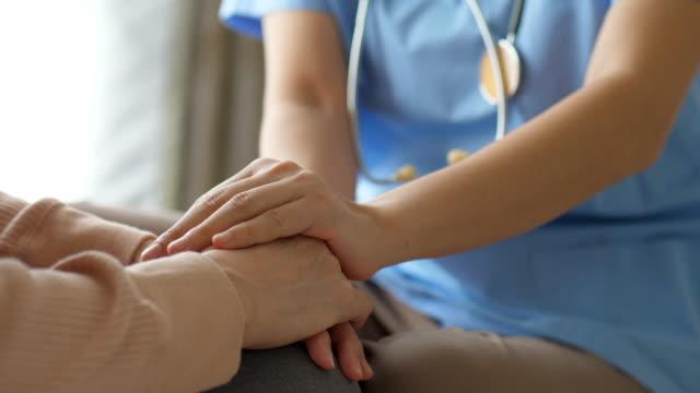 vídeos y material grabado en eventos de stock de tome el momento del cuidado, doctor mujer que sostiene la mano de la abuela mayor paciente - agarrar