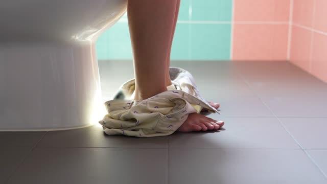 in der toilette die hose abnehmen. - sitting stock-videos und b-roll-filmmaterial
