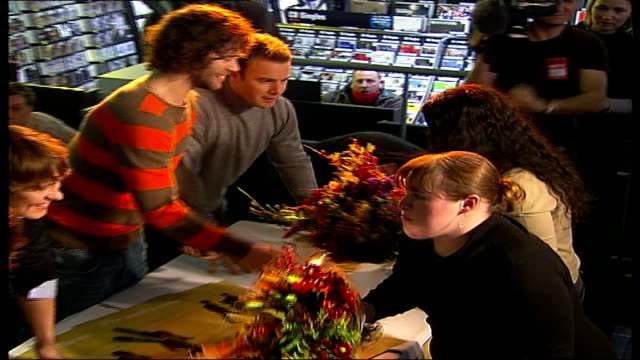 take that reform and reach number one; **mark owen interview partially overlaid** high angle view of fans handing bunches of flowers to members of... - take that stock videos & royalty-free footage