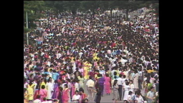 takenoko-zoku dancers wear colorful costumes as they perform in yoyogi-park. - 1980~1989年点の映像素材/bロール