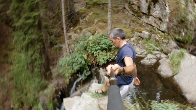 vidéos et rushes de je prends une pause. pov d'un voyageur solitaire en été. touriste masculin détendant devant une belle vue et pointant vers la vidéo de it-stock. - chute d'eau