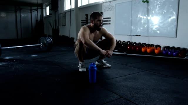 vidéos et rushes de prenant une pause dans la salle de gym - seulement des jeunes hommes