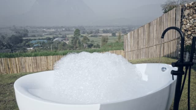 taking a bubble bath showing inside bathtub outside with the nature - bubble bath stock videos & royalty-free footage