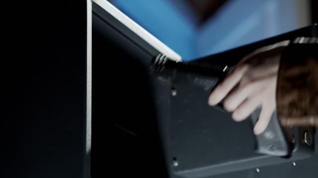国内のセーフティボックスから銃を取る - 金庫点の映像素材/bロール