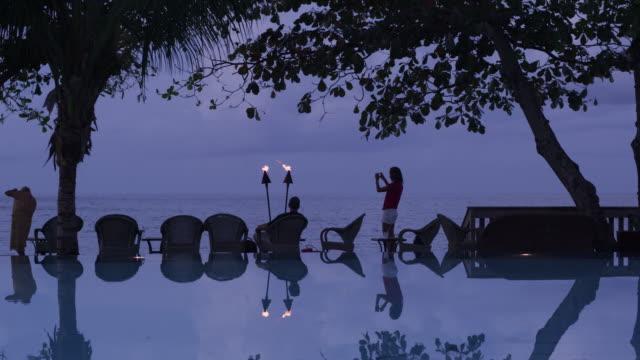 vídeos de stock, filmes e b-roll de taking a photo by a resort pool - tocha tiki
