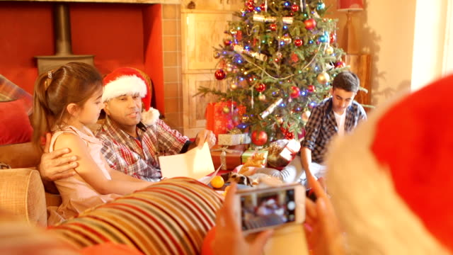 Taking a Picture of Family Opening Presents and Cards at Christmas