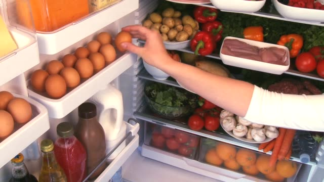 vídeos de stock e filmes b-roll de taking an egg from a full refrigerator - cheio