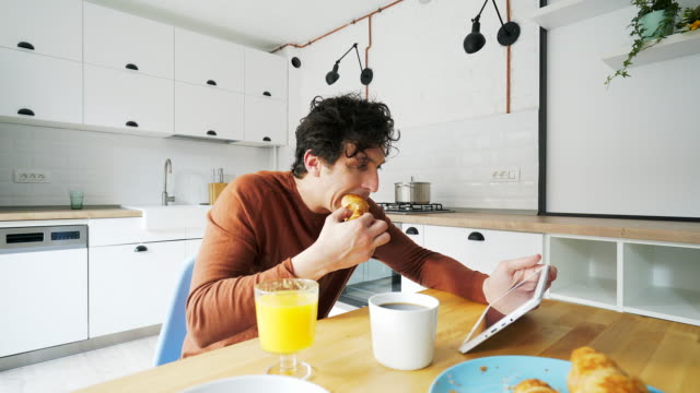 Taking breakfast while using a digital tablet.