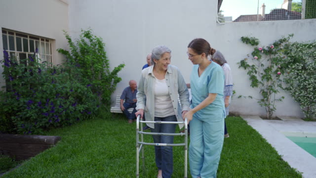 taking care of a senior patient in backyard of retirement home - walking frame stock videos & royalty-free footage
