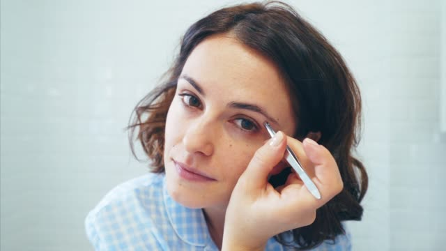 vídeos de stock e filmes b-roll de taking care of my eyebrow. - depilação