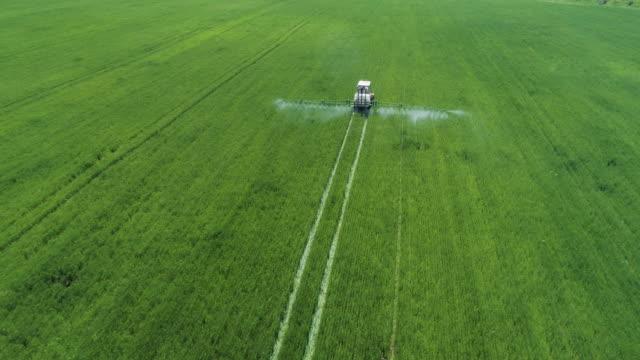 stockvideo's en b-roll-footage met het verzorgen van de crop. luchtmening van tractor die een gecultiveerd landbouwgebied bemest. - effectiviteit
