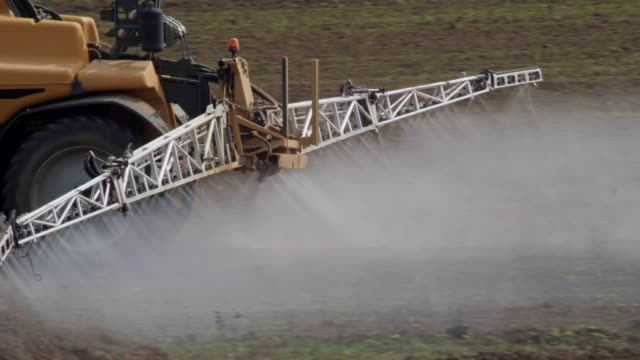 taking care of the crop. tractor fertilizing a cultivated agricultural field. - irrigation equipment stock videos & royalty-free footage