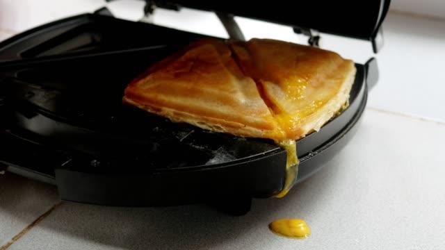 トースターからハムとチーズのトーストを取る。 - チェダー点の映像素材/bロール