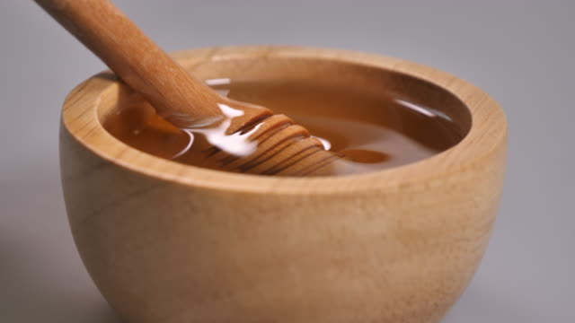 taking honey by metal spoon in wooden bowl - animal creation stock videos & royalty-free footage