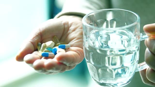 コップ一杯の水で薬を飲む - サプリメント点の映像素材/bロール