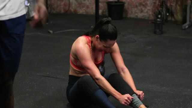 vídeos de stock e filmes b-roll de taking off her knee sleeves - encostado