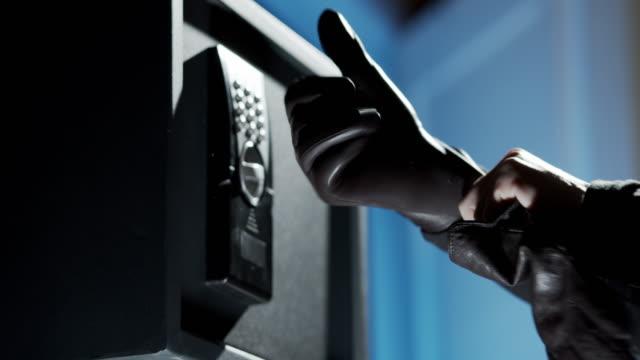 vídeos y material grabado en eventos de stock de tomando guantes de cuero frente a la caja de seguridad - ladrón de casas