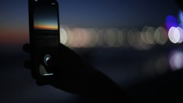 taking panorama photo of the sunset on the beach - photo manipulation stock videos and b-roll footage