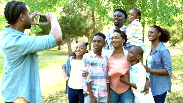 taking photo of couple, extended family joins them - aunt stock videos and b-roll footage