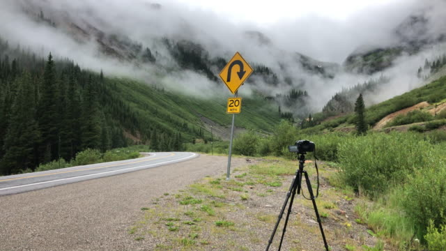 taking picture of the low mountain clouds and speed limit sign in colorado, usa, amid the 2020 global coronavirus pandemic - speed limit sign stock videos & royalty-free footage
