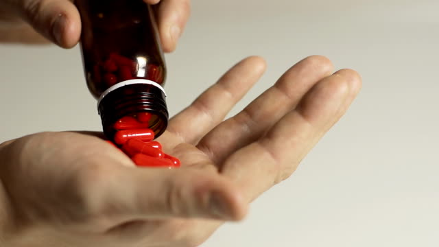 HD SLOW MOTION: Taking Pills Out Of A Bottle