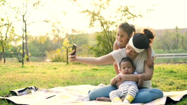 stockvideo's en b-roll-footage met selfie met mobiele telefoon nemen op picknick - twee ouders